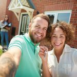 First home buyer in front of house